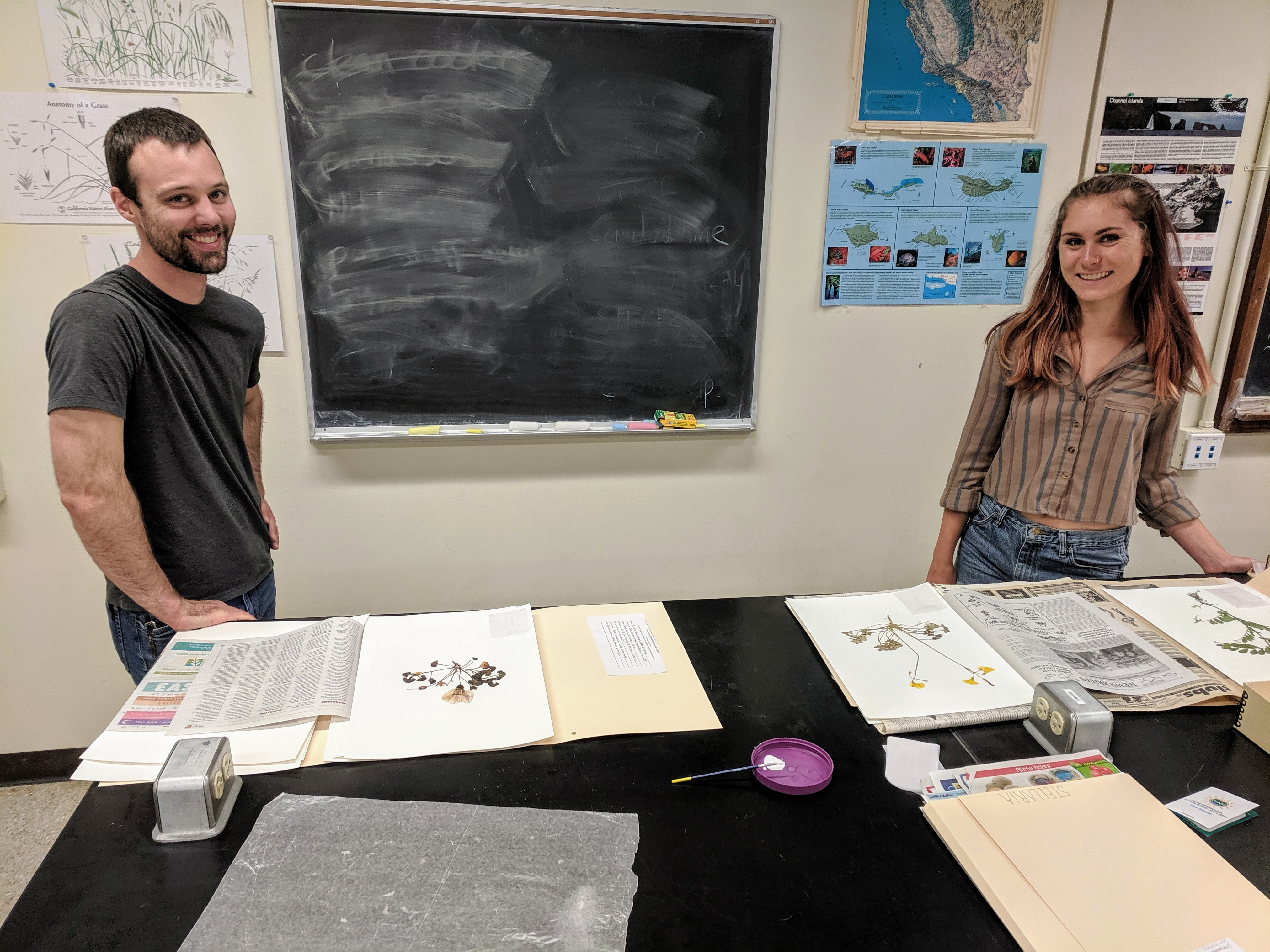 two people and some herbarium specimens